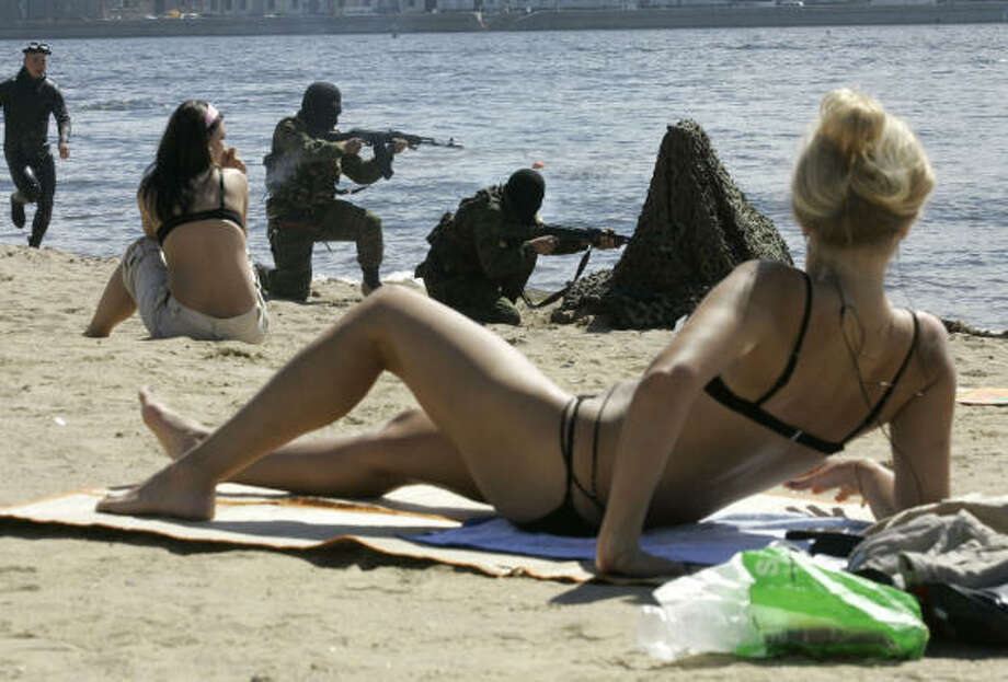 July 24| Sunbathers watch Russian marines train for Navy Day on a beach along the Neva River.  | St. Petersburg, Russia Photo: Dmitry Lovetsky, AP