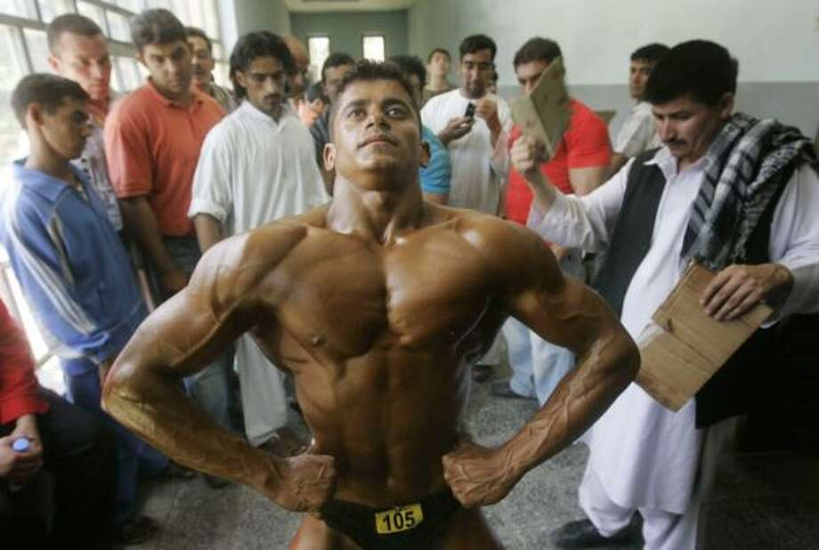 July 30| An Afghan bodybuilder flexes his muscles as he prepares for the Mr. Afghanistan national bodybuilding competition. | Kabul, Afghanistan Photo: Rafiq Maqbool, AP