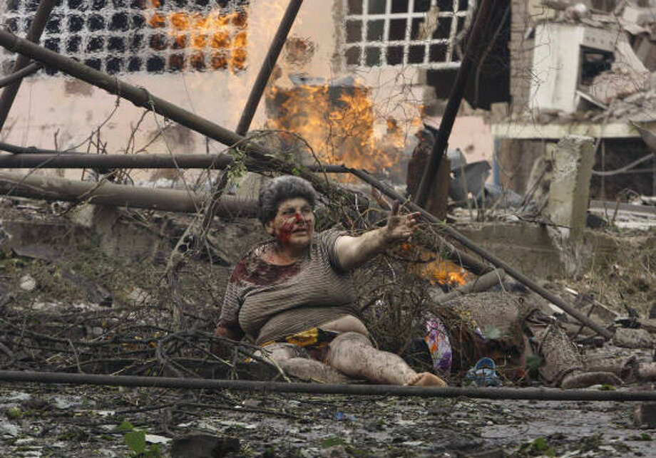Aug. 9| A wounded Georgian woman lies in front of an apartment building damaged by a Russian air strike. | Gori, Georgia Photo: GEORGE ABDALADZE, AP