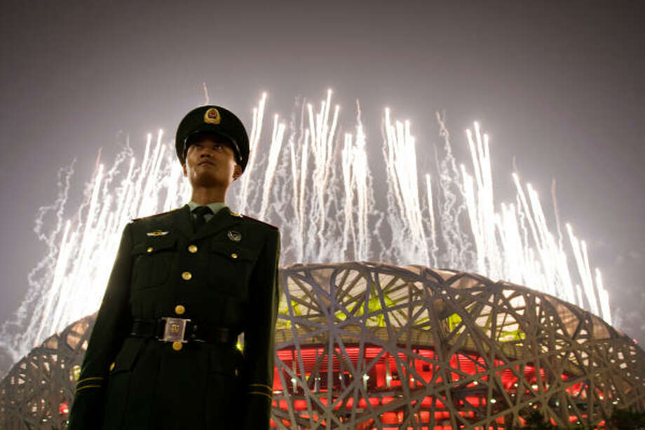 Aug. 24 | A guard stands at attention as fireworks explode over the National Stadium, also known as the Bird's Nest, during closing ceremonies for the Summer Olympic Games. | Beijing, China Photo: Smiley N. Pool, Houston Chronicle