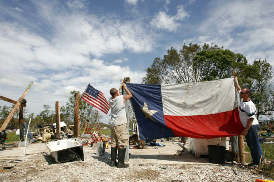 Sept. 15| Mike Casanover, left, and Jeffrey Hill hang Casanover's Texas flag amid the destruction caused by Hurricane Ike. They Casanover's flag about a mile from his destroyed home in Chambers County as residents returned to find 90  percent of the 350 homes were either destroyed or unlivable. | Oak Island, Texas Photo: Sharon Steinmann, Houston Chronicle
