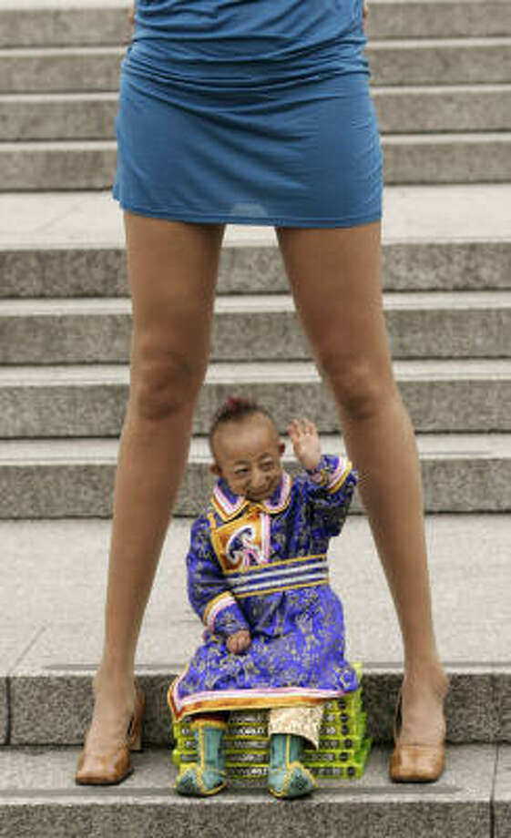 Sept. 16 | He Pingping of Inner Mongolia, the world's smallest man, sits underneath Svetlana Pankratova of Russia, the Queen of Longest Legs. | London Photo: SANG TAN, AP