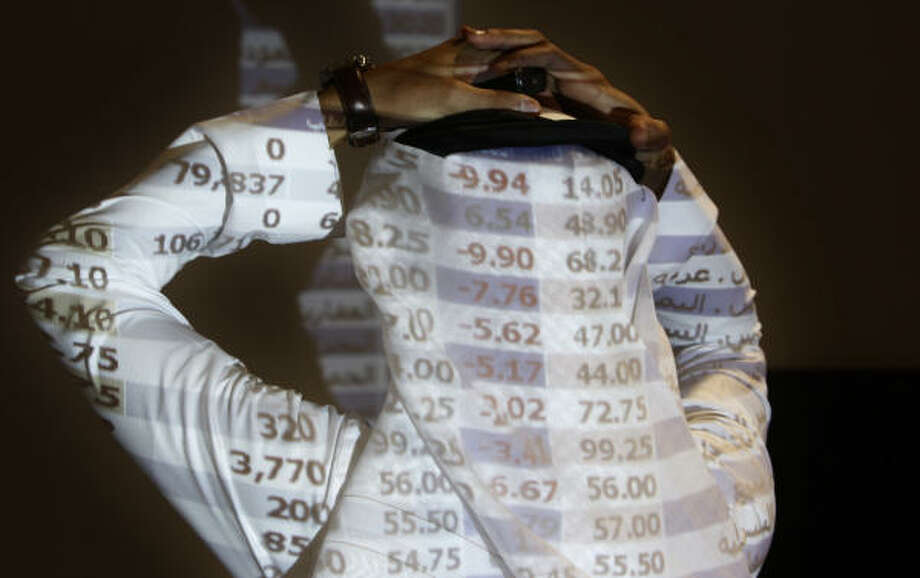 Oct. 7| A Saudi trader watches a stock market monitor as Saudi Arabia's stock market falls 7.03 percent, a drop analysts attributed to days of precipitous slides in other world markets. | Riyadh, Saudi Arabia Photo: Hassan Ammar, AP