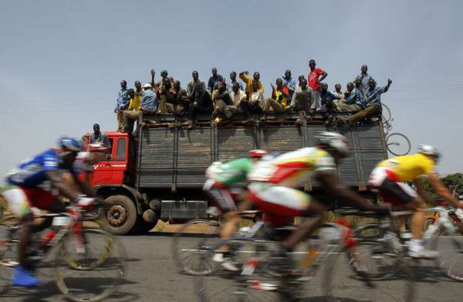 Oct. 30 | Men watch and cheer cyclists making their way between Yako and Ziniare during the 7th stage of the 22nd Tour du Faso cycling race. The Tour du Faso represents the major cycling event in the riding calendar on the African continent. | Burkina Faso Photo: CHRISTOPHE ENA, AP