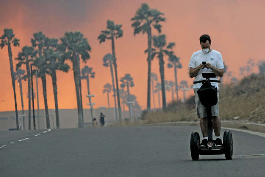 Nov. 15|  A man on a Segway uses his cell phone as wildfires glow in the distance. The Santa Ana winds fanned flames throughout Southern California, destroying hundreds of homes and causing thousands to evacuate. | Yorba Linda, California Photo: Sandy Huffaker, Getty Images