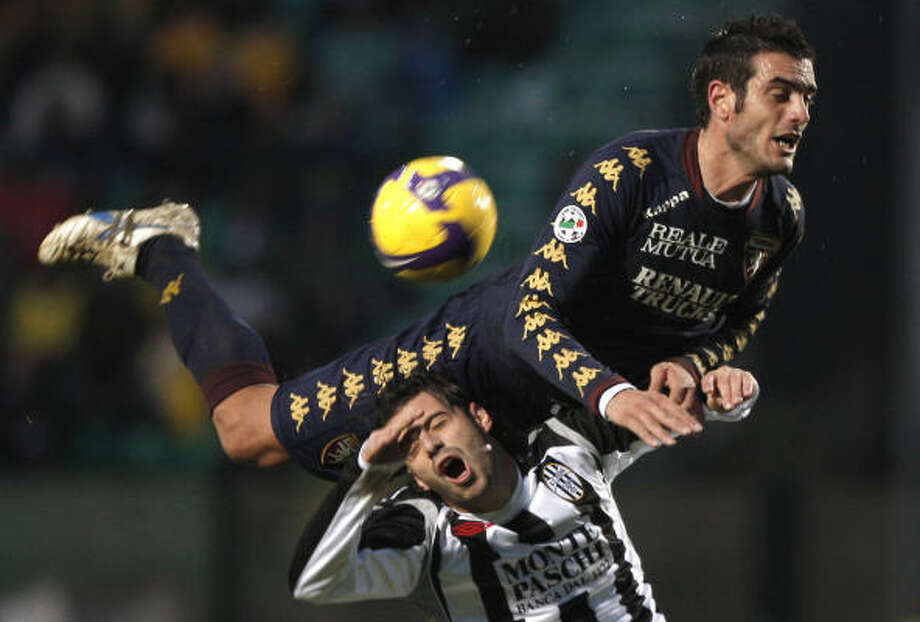 Nov. 30 | Torino's Riccardo Colombo, above, and Siena's Emanuele Calaio jump for the ball during a soccer match between Siena and Torino at the Artemio Franchi stadium. | Siena, Italy Photo: FABIO MUZZI, AP