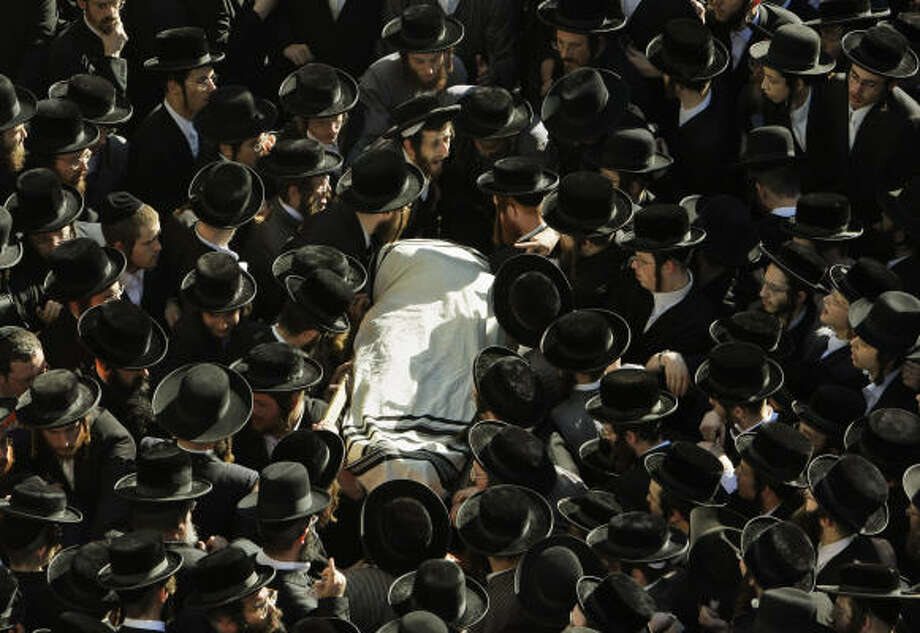 Dec. 2 | The body of Leibish Teitelbaum, 38, who was killed in the Mumbai Jewish center attack is carried by ultra-Orthodox Jewish men at his funeral procession. | Jerusalem, Israel Photo: Kevin Frayer, AP