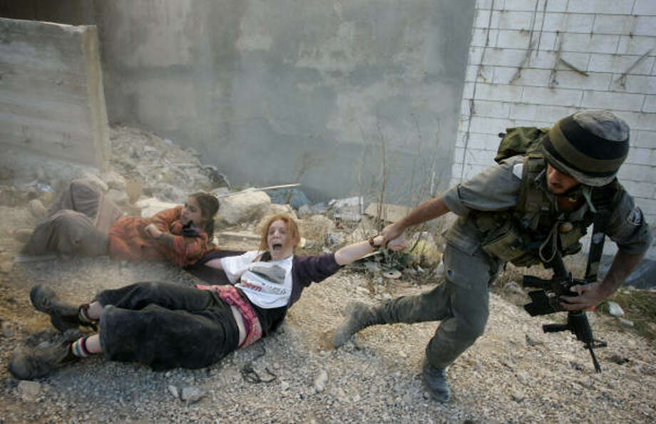 Dec. 4 An Israeli police officer drags two Jewish settlers during the evacuation of a disputed house. | Hebron, West Bank Photo: Sebastian Scheiner, AP
