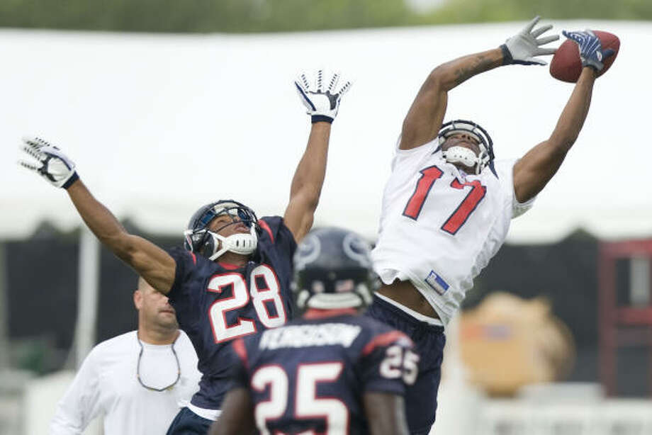 Aug. 12:Texans receiver LeRon McCoy (17) loses his grip on a high pass with cornerback Antwaun Molden (28) defending. Photo: Brett Coomer, Chronicle