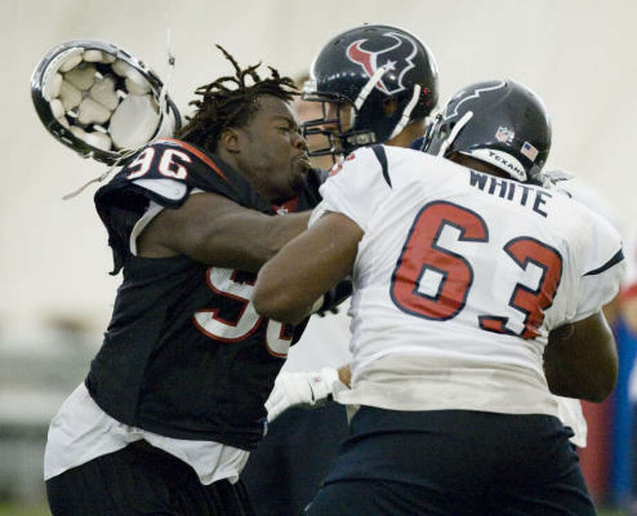 Aug. 5:Texans defensive end Earl Cochran gets his helmet knocked off by center Chris White during a pass rush drill. Photo: Brett Coomer, Chronicle