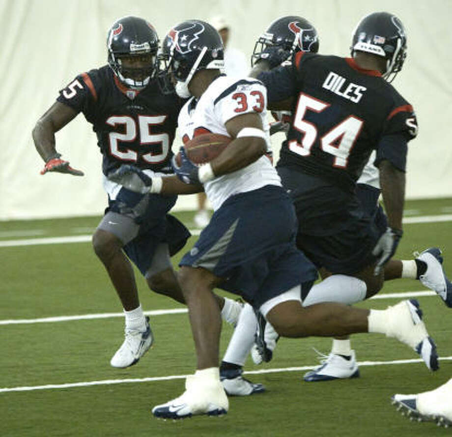 Aug. 1:Newly acquired Texans running back Mike Bell rushes toward safety Nick Ferguson (25) as Zac Diles (54) gets blocked off the play. Photo: Brett Coomer, Chronicle