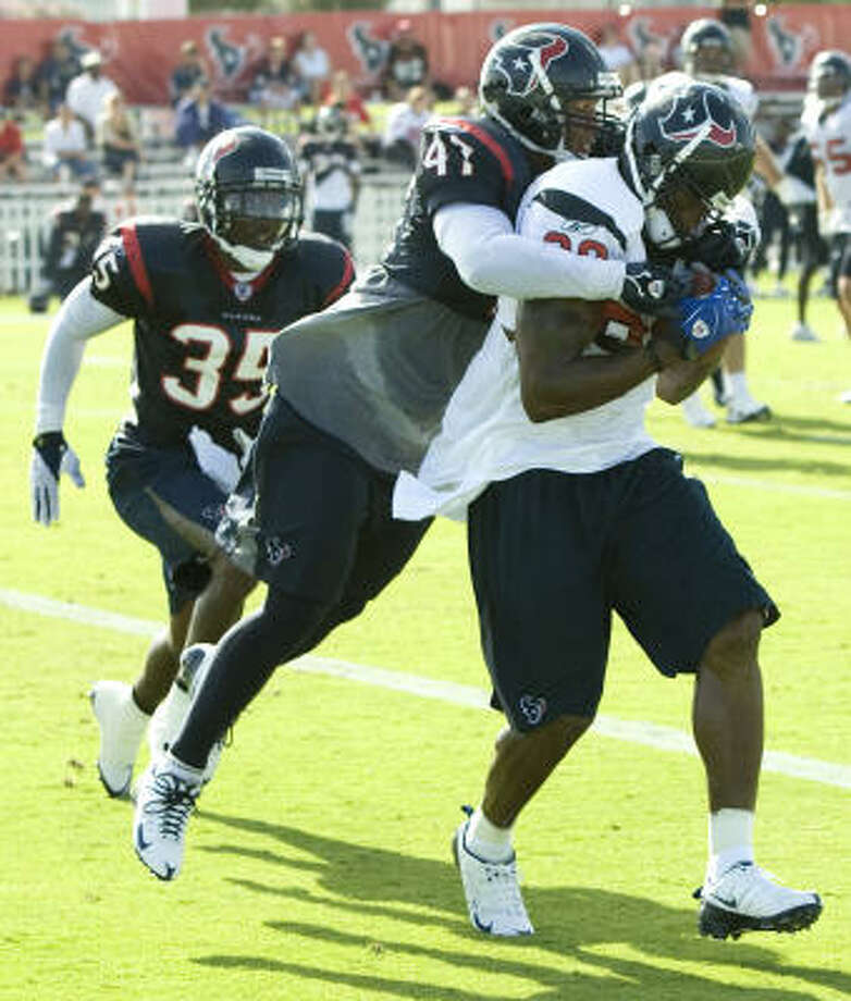July 29:Texans free safety Will Demps wraps up receiver Andre Johnson after Johnson made a catch in the end zone. Photo: Brett Coomer, Chronicle
