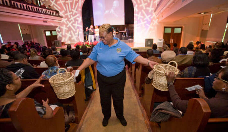 Brenda Young helps pass collection baskets during services at St. John's Methodist Church downtown. The church has a diverse congregation and has several homeless ministries including Bread of Life, which feeds homeless people meals in the downtown area. Photo: Steve Campbell, Chronicle
