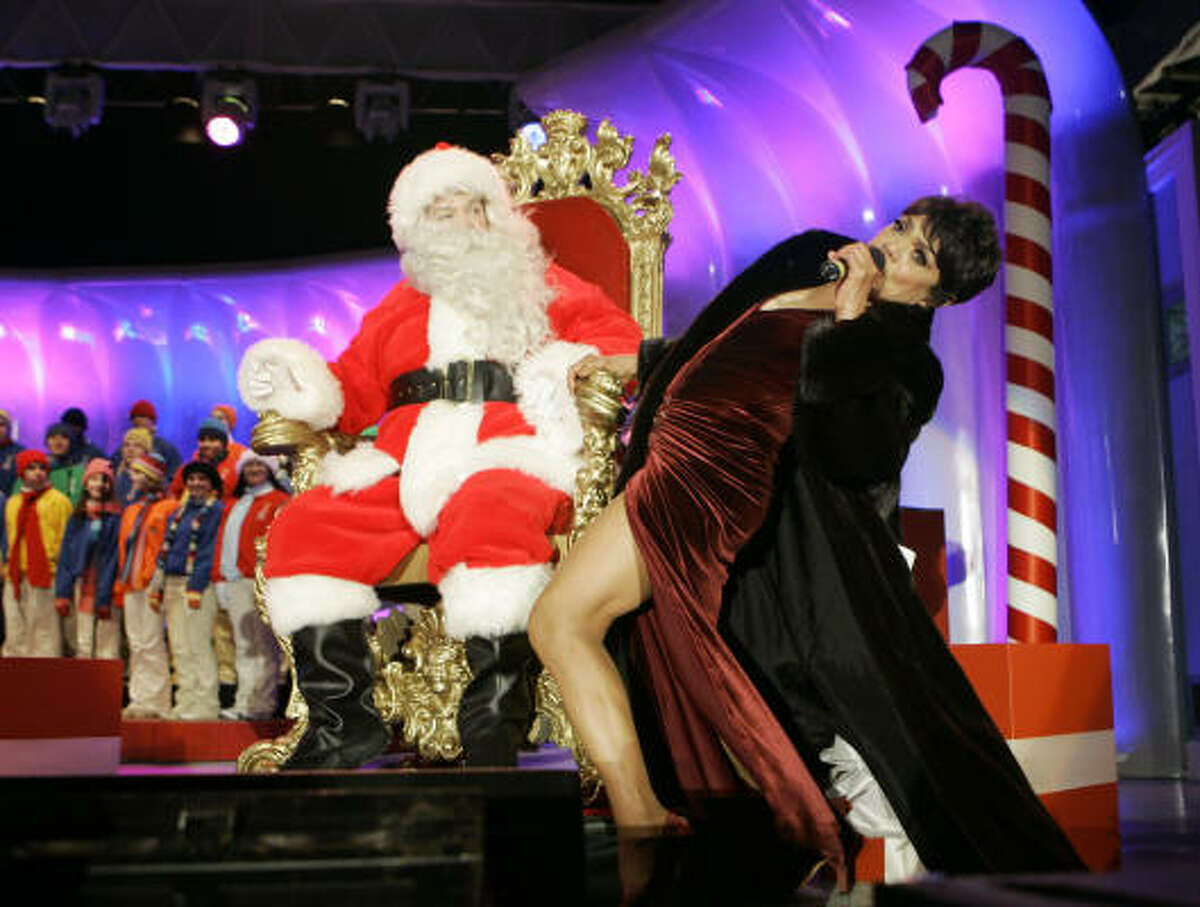 **FILE** This Dec. 7, 2006 file photo shows Brad Oscar, dressed as Santa Claus, watching Eartha Kitt perform during the Christmas Pageant of Peace Opening Ceremony on the Ellipse in Washington. A family friend says Kitt has died Thursday, Dec. 25, 2008 of colon cancer. She was 81.