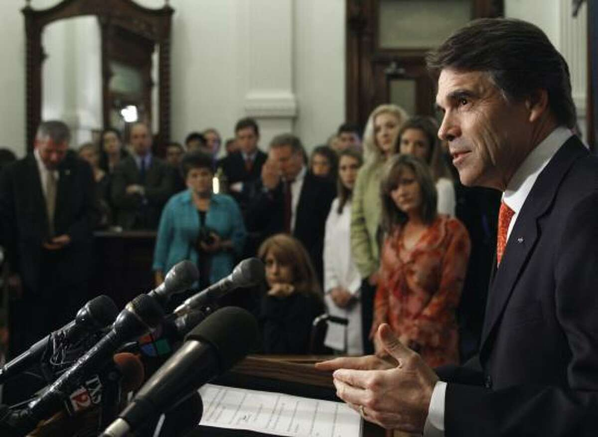 Gov. Rick Perry, foreground, speaks during a news conference Tuesday in Austin. Gov. Perry announced that he would let stand a bill that blocks state officials from following his order requiring an anti-cancer vaccine for sixth-grade schoolgirls.