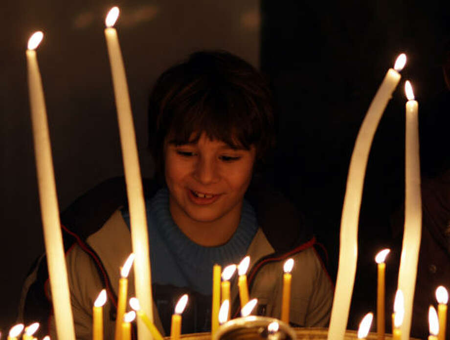 A Greek Orthodox boy lights candles during the Christmas mass at the Patriarchal Cathedral of St. George in Istanbul, Turkey, Dec. 25. Ecumenical Patriarch Bartholomew I, the spiritual leader of the world's Orthodox Christians, led hundreds of worshippers at a crowded Christmas service.  Share your Christmas photos here. Photo: Murad Sezer, AP