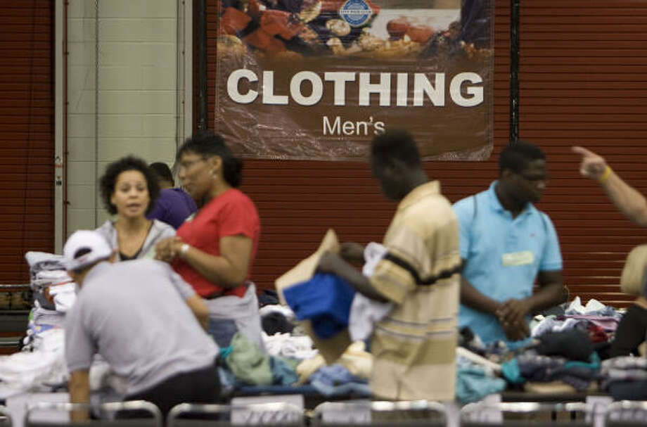 Volunteers hand out men's clothing to guests during the City Wide Club of America's 30th annual Christmas Eve Big Feast at the George R. Brown Convention Center. Photo: James Nielsen, Chronicle
