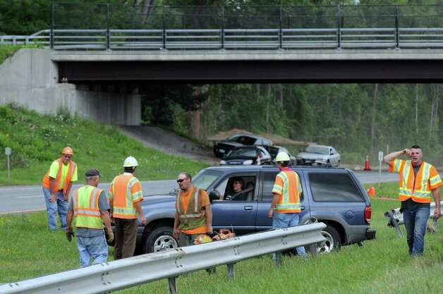 A driver leaves the westbound lane of the Thruway while driving across the median to the eastbound lane between exits 23 and 24 during a gas main break on Wednesday Aug. 10, 2011 in Albany, NY. The break is just beyond the bridge in the background, at left. Workers had cut away the guardrail to make the turnaround for vehicles minutes earlier. (Philip Kamrass / Times Union) Photo: Philip Kamrass / 00014197A