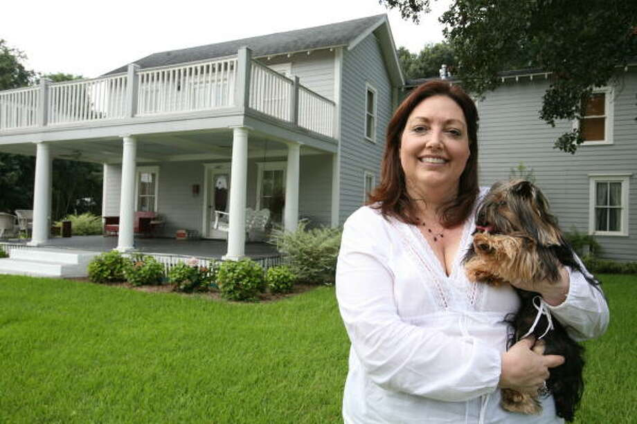 Jennifer Howard holds her Yorkshire terrier, Teddy, at her home on Avenue C in Katy.  She is gathering history about her home iin hopes it will get on the National Register of Historic Places. Photo: Suzanne Rehak, For The Chronicle