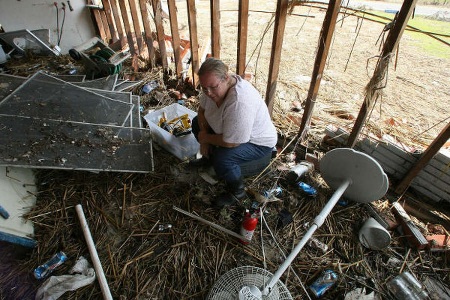 Melancholy | Dianne Brookshire sits in her home among her possessions, now mixed with grass and debris. | Sept. 19 | Bridge City Photo: Billy Smith II, Houston Chronicle