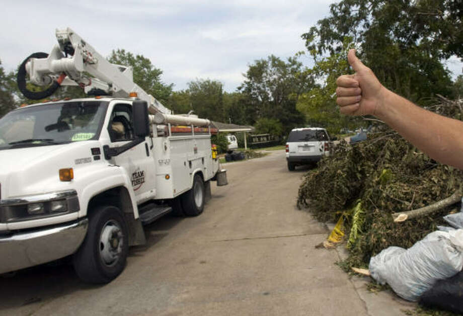 Welcome sign | Raul Casarez gives a group of power linesmen from Florida-based Team Fishel a thumbs up as they drive down his street. At least 6,000 additional linesmen and other workers were brought in from all over the United States to help restore power to the area. | Sept. 17 | Houston Photo: Johnny Hanson, Houston Chronicle