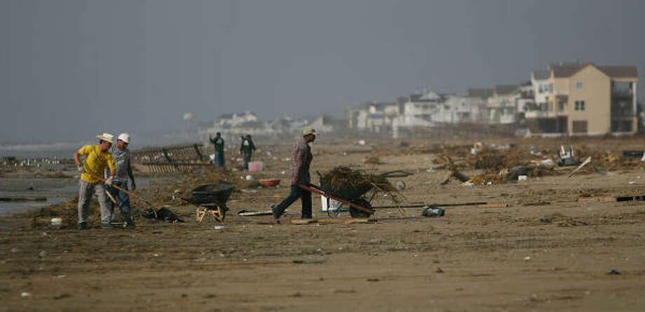Beach duty | Crews wheel out debris near Indian Beach in the West End. | Sept. 23 | Galveston Photo: Mayra Beltran, Houston Chronicle