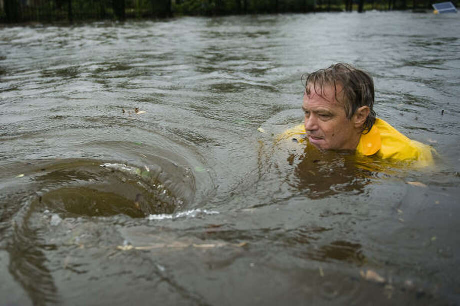 Whirlpool | Greg Schenck struggles to remove debris from a drain causing flooding on North Main just north of downtown. | Sept. 13 | Houston Photo: Smiley N. Pool, Houston Chronicle