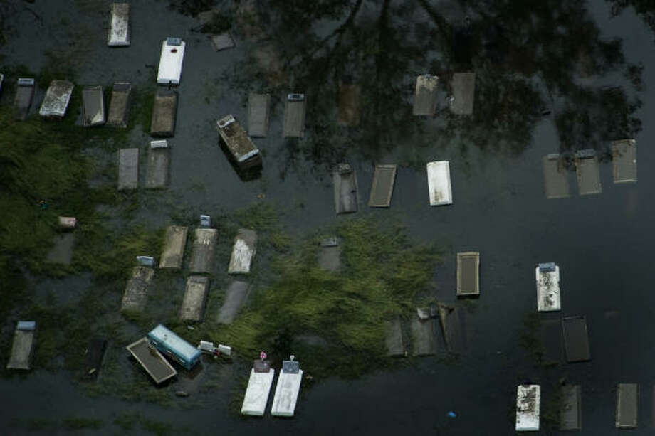 Unearthed | Murky water inundates a cemetery. | Sept. 14 | Orange Photo: Smiley N. Pool, Houston Chronicle