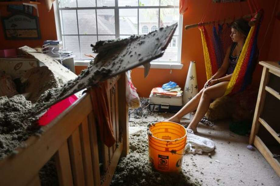 No place safe | Alison Naquin, 14, takes a measure of all the damage to her bedroom. Naquin was in the game room with the rest of her family when the roof caved in over her bed. | Sept. 13 | Pearland Photo: Mayra Beltran, Houston Chronicle