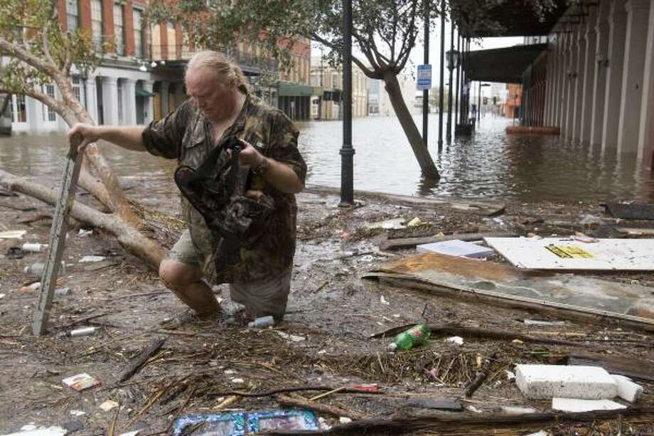 Murk and mire | Tom LeCroy wades through debris-choked floodwaters along The Strand after riding out the storm on the historic street. LeCroy's restaurant suffered major flood damage. | Sept. 13 | Galveston Photo: Brett Coomer, Houston Chronicle