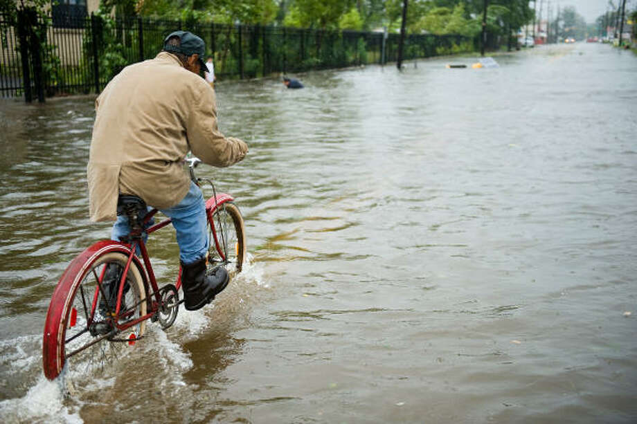 Hard ride | A man pedals his bicycle through floodwaÂters on North Main just north of downtown. | Sept. 13 | Houston Photo: Smiley N. Pool, Houston Chronicle