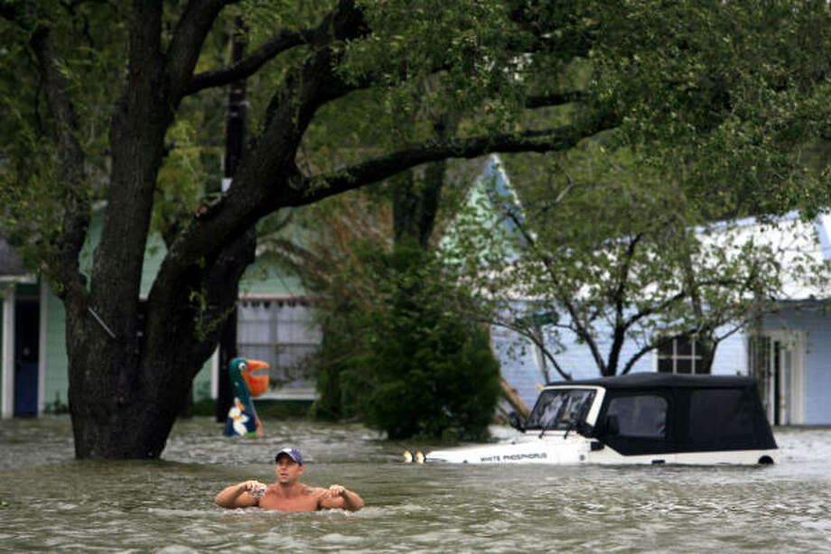 In too deep| Chris Symank leaves his flooded Jeep after checking on a friend's house. He said he forgot about the road's dip in that spot until it was too late. | Sept. 12 | Kemah Photo: Eric Kayne, Houston Chronicle