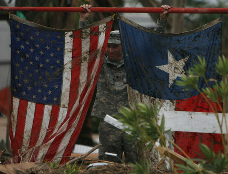 Tattered   | Spc. Scott Hayes with the Texas Army National Guard holds up a muddied set of flags found in the destruction as guardsmen conduct search and rescue operations. | Sept. 14 | Galveston Photo: Sharon Steinmann, Houston Chronicle