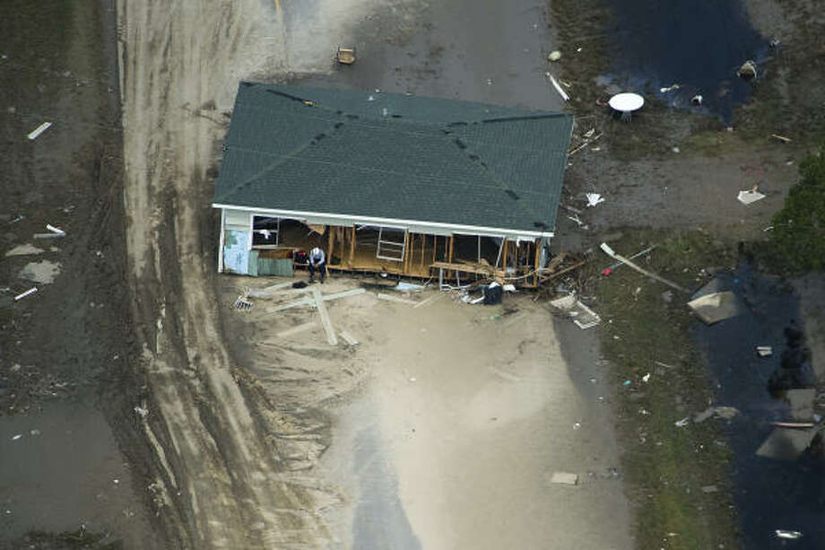 Weary   A search worker rests on the porch of a house pushed askew during the hurricane.   Sept. 15   Crystal Beach Photo: Smiley N. Pool, Houston Chronicle