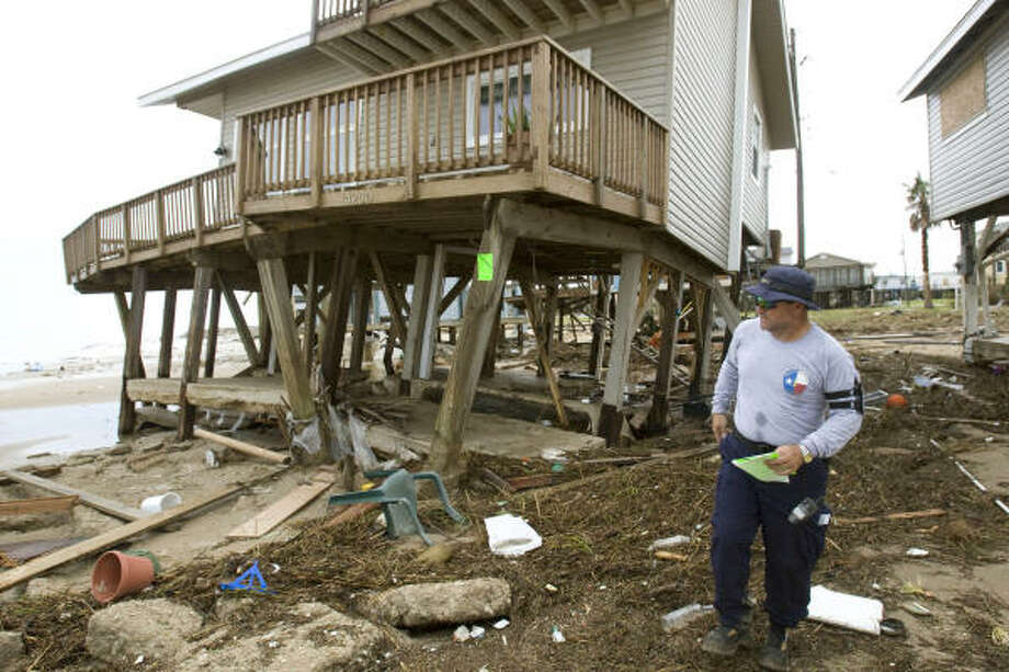 Still upright | A resident surveys damage near a constellation of battered beach homes. | Sept. 14 | Galveston Photo: Brett Coomer, Chronicle