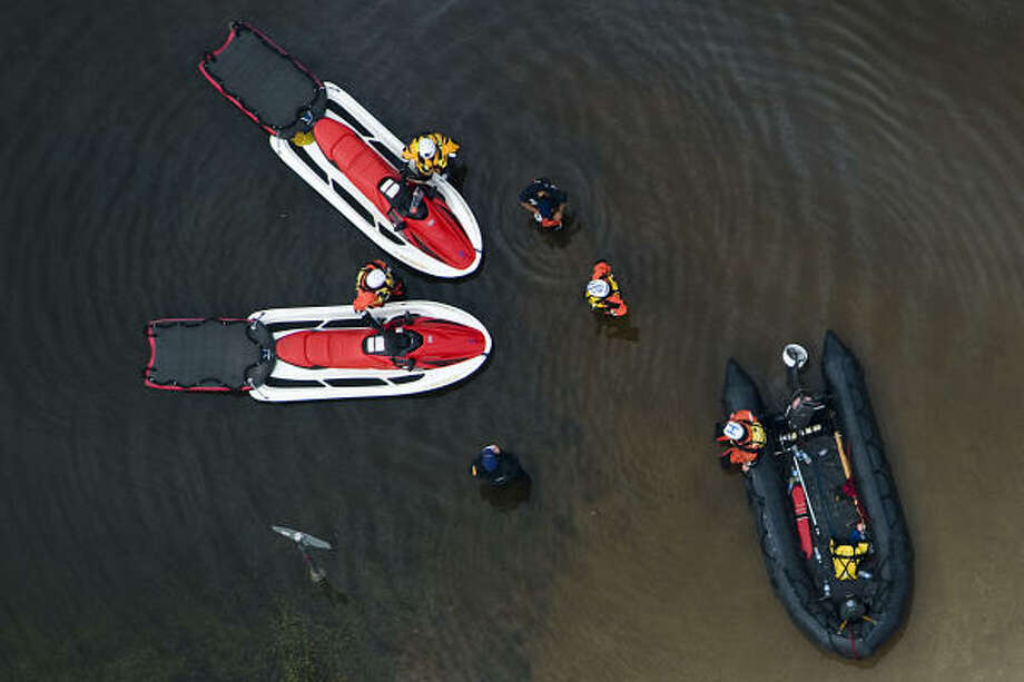 Plan of action | Rescue boats convene near a stop sign on a flooded road. | Sept. 14 | Bridge City Photo: Smiley N. Pool, Houston Chronicle