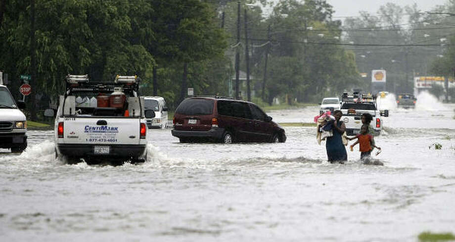 Perilous walk | A woman and her children wade through floodwaters on Yale in Independence Heights. | Sept. 14 | Houston Photo: Karen Warren, Houston Chronicle