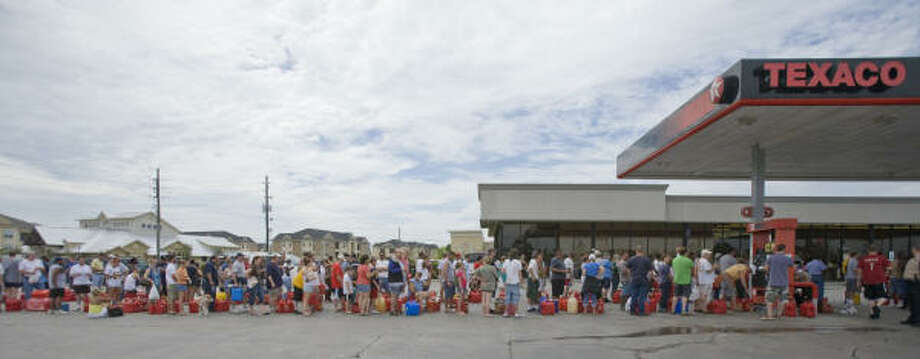 Long wait | Customers lined up for as long as three hours to buy gas at Texaco, one of the few open stations. The station used a generator to keep powered up. | Sept. 14 | Spring Photo: Steve Campbell, Houston Chronicle