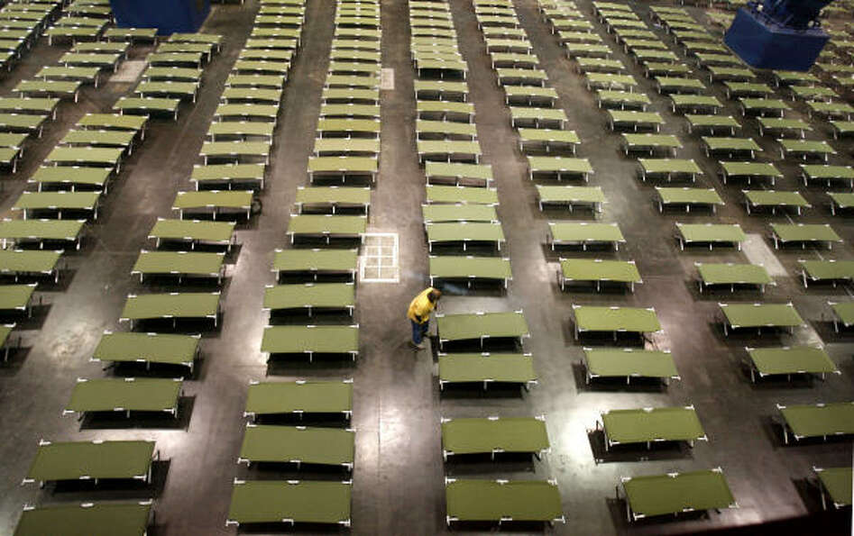 Sea of cots   | A volunteer arranges cots at the George R. Brown Convention Center,