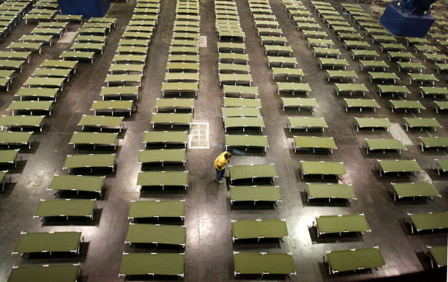 Sea of cots | A volunteer arranges cots at the George R. Brown Convention Center, where the Red Cross and other organizations set up a staging center for evacuees. | Sept. 15 | Houston Photo: Karen Warren, Houston Chronicle