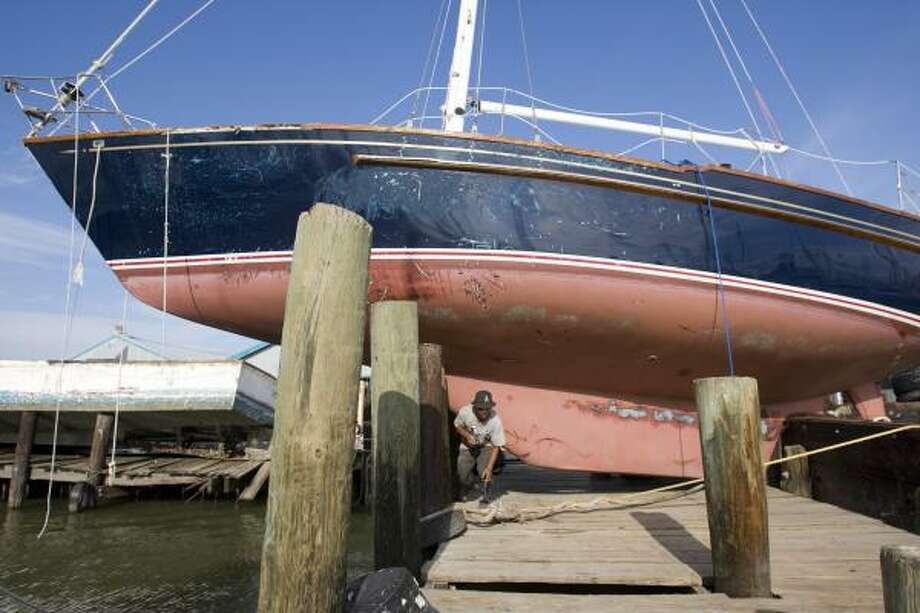 Docked | Anh Ngo walks under a sailboat that washed up on the dock at a shrimp boat marina. | Sept. 15 | Galveston Photo: Brett Coomer, Houston Chronicle
