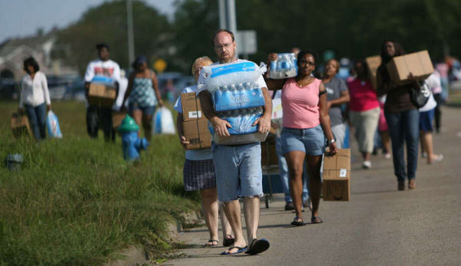 Loaded down| Residents return to their vehicles after receiving their allotment of FEMA supplies. | Sept. 15 | Houston Photo: Mayra Beltran, Houston Chronicle