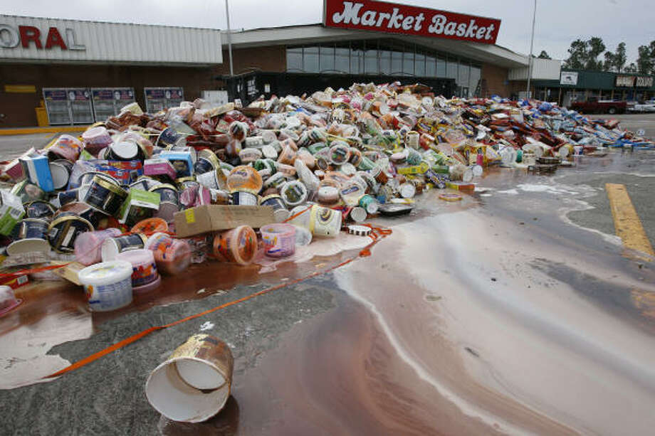 Inedible | Thawed foodstuffs pulled from the shelves of the Market Basket grocery are piled high in front of the store. | Sept. 15 | Winnie Photo: James Nielsen, Houston Chronicle