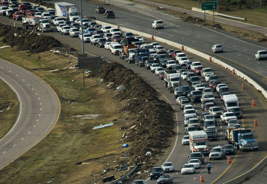 Slow return | Traffic backs up on Interstate 45 just before the Galveston Causeway as evacuees are allowed back on the island for the first time. It was lines like these that caused island officials to reverse the look-and-leave policy. | Sept. 16 | Galveston Photo: Smiley N. Pool, Houston Chronicle