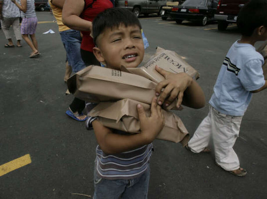 Safekeeping  | Steven Merlos, 3, tries to keep a tight grip on the MREs that his family got from a FEMA distribution site set up at the Willow Creek Apartments. |Sept. 18 | Houston Photo: Julio Cortez, Houston Chronicle