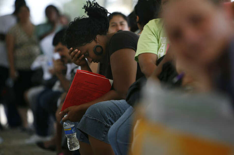 Looking for help | Along with hundreds of other people, Crystal Adams waits to apply for food stamps at the Health and Human Services office on Telephone Road. She and her boyfriend, who have a 2-month-old child, haven't been able to return to their jobs since the hurricane. | Sept. 22 | Houston Photo: Sharon Steinmann, Houston Chronicle