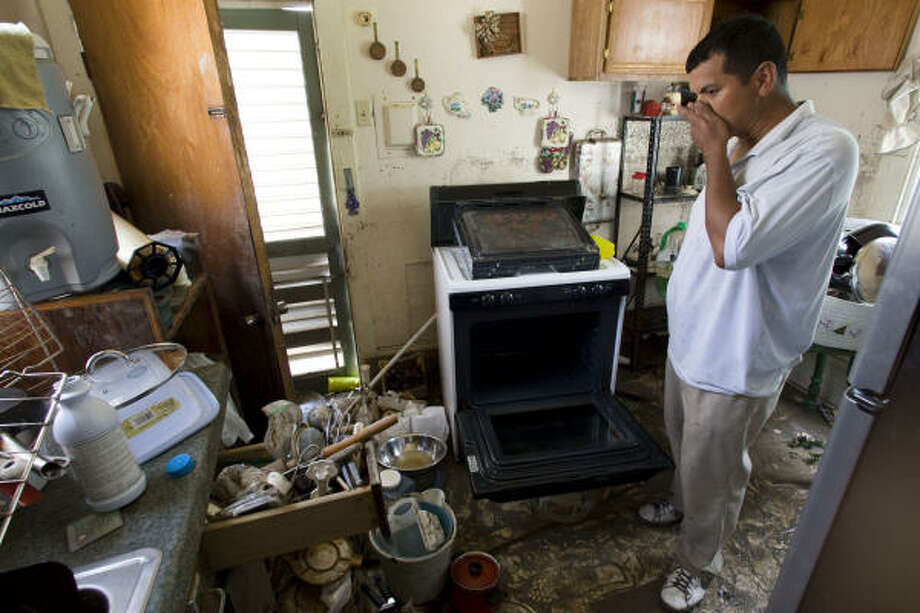 In shambles  | Rolando Garza takes a break from cleaning his moldy and muddy kitchen. Garza said his family lost everything after floodwaters surged into his home. | Sept. 23 | Galveston Photo: Brett Coomer, Chronicle