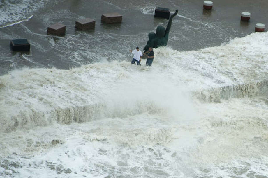 Memories| Waves crash over the seawall as two men walk near a memorial to the Great Storm of 1900, which killed as many as 8,000 people. | Sept. 12 | Galveston Photo: Smiley N. Pool, Houston Chronicle
