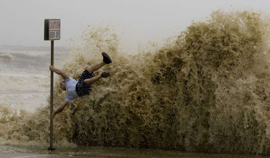 Double take| Travis Postany hangs on to a sign post as he clowns around while a wave crashes into the Seawall. | Sept. 12 | Galveston Photo: Brett Coomer, Houston Chronicle