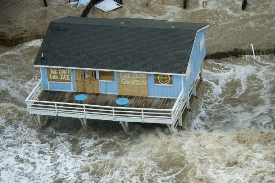 """Common sentiments  The messages """"We don't like Ike"""" and """"God bless Galveston"""" are scrawled on plywood covering the windows of a beach house.   Sept. 12   Galveston Photo: Smiley N. Pool, Houston Chronicle"""